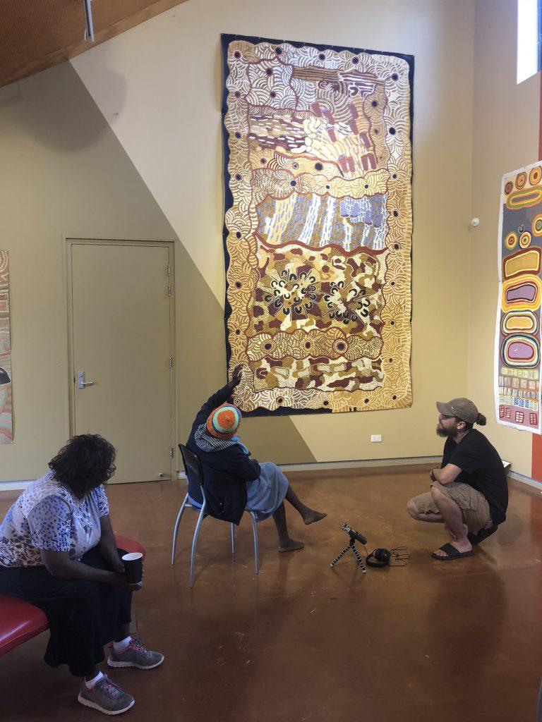 Debra and Betty West discussing Betty's painting of the Wati Kutjarra and Tjintjintji at Nyirrnyirrpungu with Victorian Program Manager Daen Sansbury Smith, in preparation for a Creative Digital Storytelling Program in Warburton